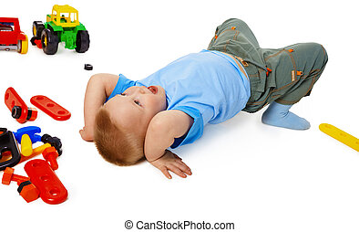 A little boy fooling around on the floor among the toys