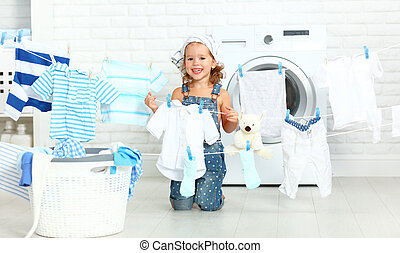 child fun happy little girl to wash clothes and laughs in...
