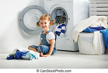 child fun happy little girl to wash clothes in laundry room