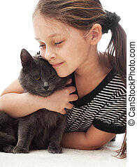 child gently hugs a gray cat