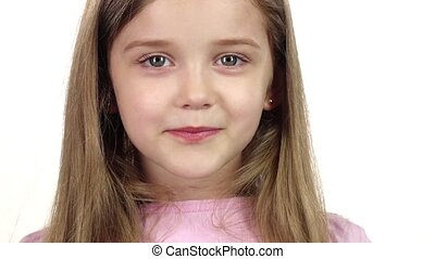 Child genuinely smile at the camera. White background. Close up. Slow motion
