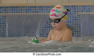 Child getting hydromassage in pool - Little boy playing with...
