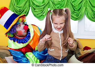 Child girl and clown playing on birthday party.