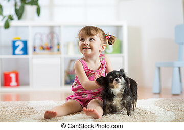 Child girl and her dog play in nursery