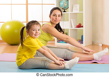 Child girl and her mother doing gym exercise at home - Child...