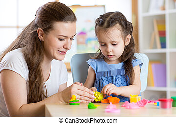 child girl and woman playing colorful clay toy at nursery or kindergarten