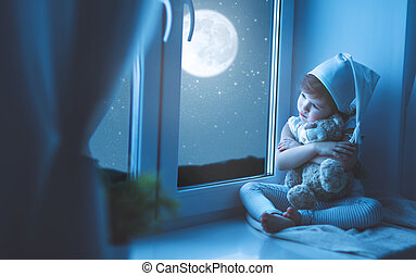 child girl at window dreaming starry sky at bedtime