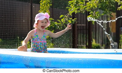 Child girl bathes in a pool under the spray of water.