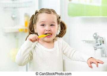 child girl brushing teeth in bathroom