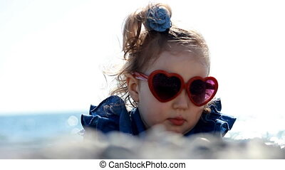 Child girl by the sea on beach on a windy sunny day with glasses in the form of a heart. The concept of love and happiness