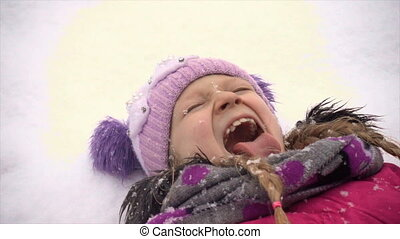 child girl catching a snowflakes with her tongue