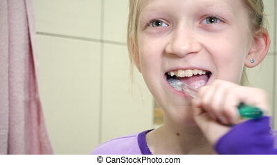 child girl cleaning teeth at the bathroom