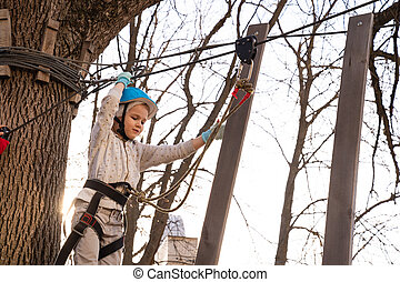 child girl climb in rope Park in the spring