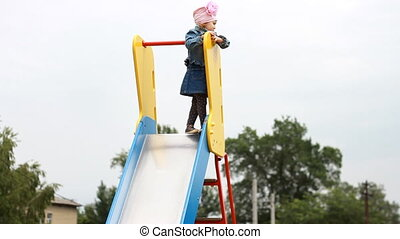 Child girl climbed high up. play on the playground