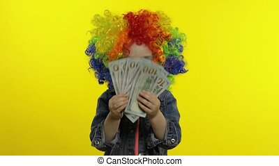 Child girl clown in colorful wig making silly faces with ...