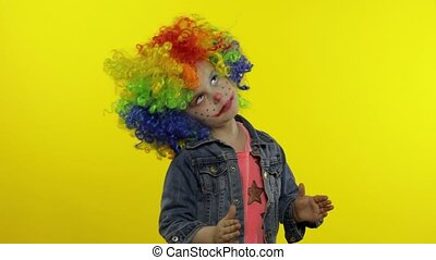Child girl clown in wig making silly faces. Having fun, ...