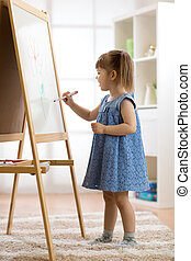 Child girl drawing at home