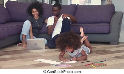 Child girl drawing on warm floor with happy black parents -...
