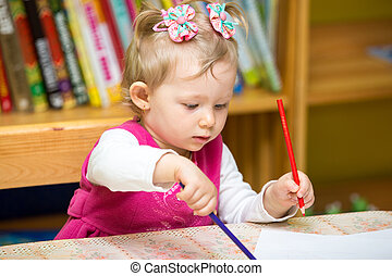 Child girl drawing with colorful pencils in preschool at the table in kindergarten