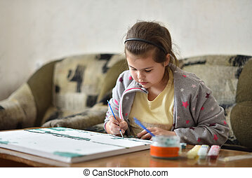 Child girl draws a picture with paints at home