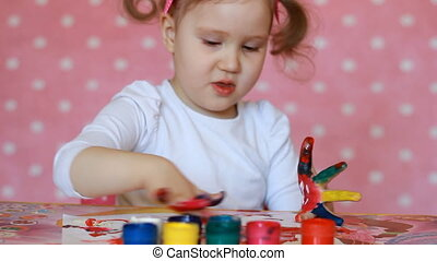 Child girl draws by brush and paint. Baby art. Gouache and...