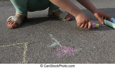 Child girl draws with chalk on asphalt close up outdoor