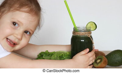 Child girl drinking green vegetable smoothies. Concept of...