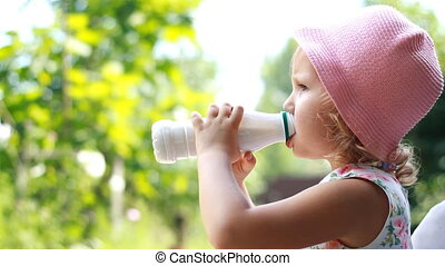 Child girl drinks a milk drink from a bottle or kefir,...
