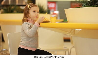 Child girl eating fast food french fries in a cafe.
