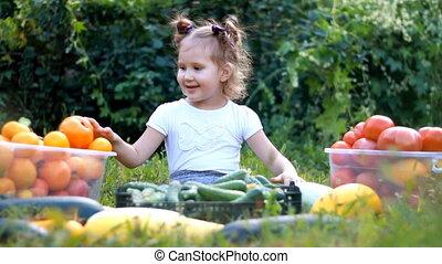 Child girl eating vegetables. Harvest of farming. The baby...