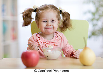 Child girl eating with spoon
