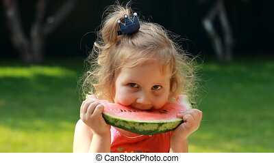 Child girl eats a watermelon. Baby eating food in summer. Close-up portrait