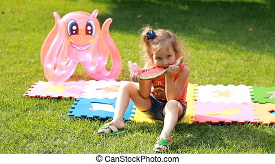 Child girl eats a watermelon. Baby eating food in summer. Picnic on green grass or lawn