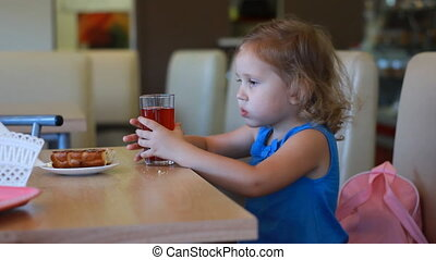 Child girl eats fast food and drinks juice in a cafe