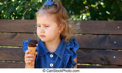 Child girl eats ice cream cone with chocolate In the park on a sunny summer day. Portrait of a baby close-up