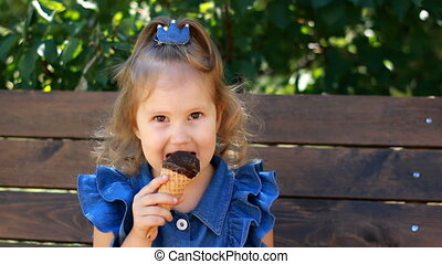 Child girl eats ice cream cone with chocolate In the park on...