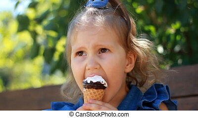 Child girl eats ice cream cone with chocolate In the park on a sunny summer day. Portrait of a baby close-up.