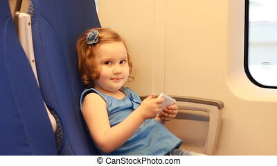 Child girl entertaining with smartphone in train.