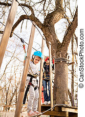 child girl fears climb in rope Park in the spring