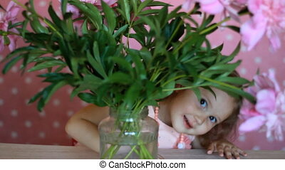 Child girl hides in a bouquet with peonies. Baby playing...