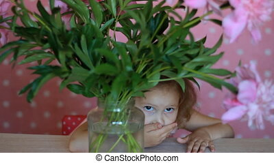 Child girl hides in a with peonies. Baby playing with pink...