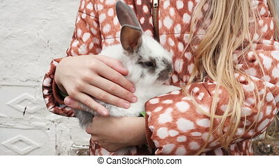 child girl holding a rabbit at her hands