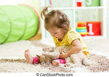 Child girl holding her cat kitten on the floor