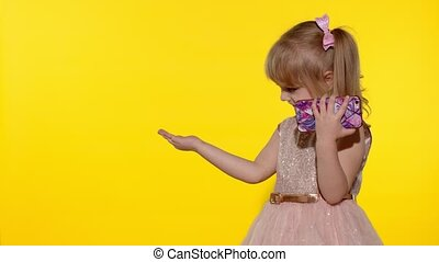Child girl using and holding smartphone. Kid pointing at something with hands, showing a product, smiling and offering an imaginary object. Place for your logo, text. Copy space. Yellow background