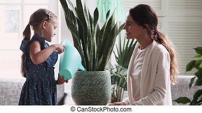 Child girl holding watering can water house plant helping mom
