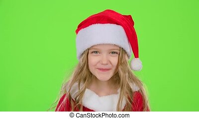 Child girl in a beautiful suit and a red New Year's cap smiles. Green screen