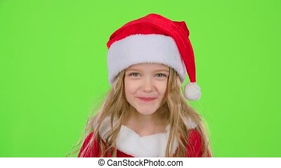 Child girl in a beautiful suit and a red New Year's cap smiles. Green screen. Slow motion