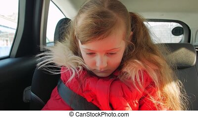 Child girl in a car seat waiting for parents
