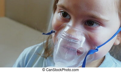Child girl in a mask for breathing inhalation medication....