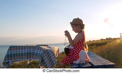 Child girl in a straw hat and dress sitting on vintage bench and taking a picture. Cute kid with soft pink rabbit toy looking at notebook in hands on sea nature lanscape background. Friendship concept